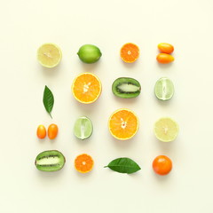 Fruit background. Summer concept. Colorful fresh citrus fruit on a light pastel yellow background table. Orange, tangerine, lime, kiwi. Flat lay, top view, copy space