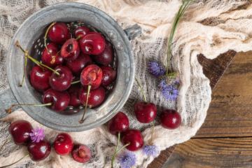 Fresh cherries on dark wooden background. Summer and harvest concept. Vegan, vegetarian, raw food.