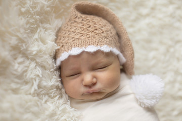 A little child in a white diaper and cap lies on a beige background. Newborn fashion