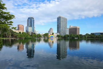 Downtown Orlando skyline glistens as it reflects in the clean waters of Lake Eola.   Lake Eola Park is a popular downtown tourist attraction.