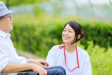 高齢男性と会話する女性