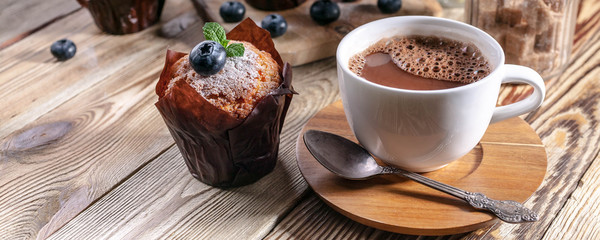 Photo sur Toile Chocolat Muffins with blueberries and a cup of hot chocolate on a wooden background. homemade baking. Banner