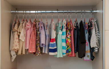 colorful brand new baby girl clothes inside closet
