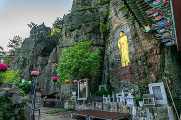 Golden Buddha image statue craft on the rock cliff