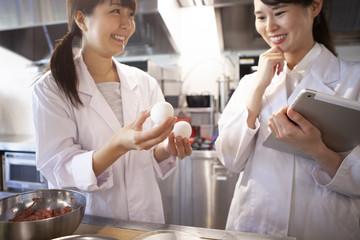 栄養士たちが笑顔で卵を手に取っている