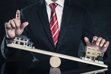 ビジネスマンとシーソーに乗っている住宅模型