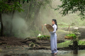 Beautiful woman wearing a hat Dress Ao Dai traditional Vietnamese dress standing in the forest.