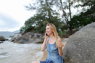 Fotobehang Young caucasian girl sitting on sand near sea and stones, speaking by smartphone. Concept of modern technology and resting on beach in morning.