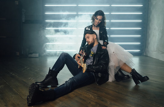 Wedding in the style of rock. Rocker or Biker wedding. Guys with stylish leather jackets. It's a rock'n'roll baby Sweet couple in a photo studio. Steep shooting with electric guitar and smoke.