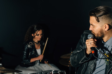 Wedding in the style of rock. Guys with stylish leather jackets. It's a rock'n'roll baby Sweet couple in a music studio. The bride plays the drums, and the groom sings.