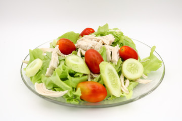 Salad with chicken and fresh vegetables isolated on white background.
