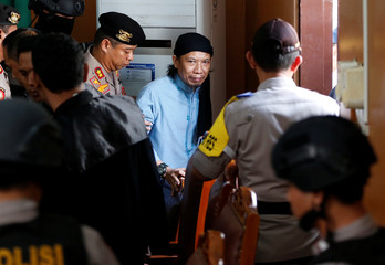 Islamic cleric Aman Abdurrahman leaves a court following his verdict in Jakarta