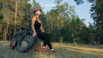 Fat bike also called fatbike or fat-tire bike in summer riding in the forest. Beautiful girl and her bicycle in the forest. She poses and smiles to the operator. Very positive and provocative.
