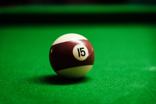 Billiard ball in a green pool table focus on the number fifteen brown and white ball