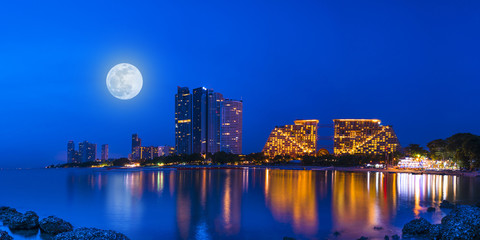 Panorama Colorful light Pattaya city in night time with full moon