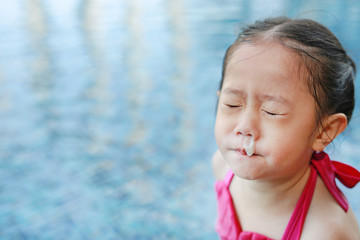 Mucus flowing from nose of little asian child girl while swimming at pool.