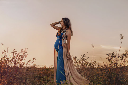 happy pregnant woman walking on a field at sunset