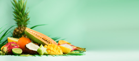 Assortment of exotic fruits on turquoise background. Banner. Detox, vegan food, summer concept. Papaya, mango, pineapple, carambola, dragon fruit, kiwi, orange, melon, coconut, lime over palm leaves.
