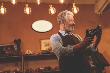 An elderly shoemaker with a shoe