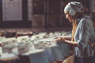 Attractive girl listening to music in a music store