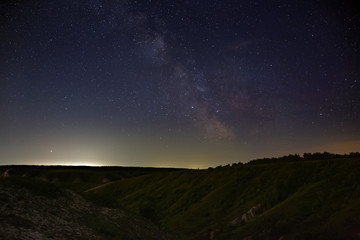 Stars of the Milky Way in the night sky. A view of the starry space background sunset illuminated the horizon.
