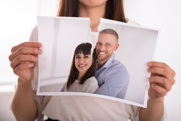 Woman Tearing Photo Of Happy Couple