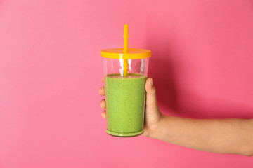 Female hand holding glass with tasty smoothie on color background