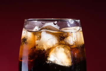 A glass of cola beverage with a salt. On a red background.