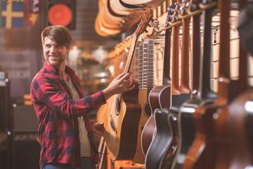 Spoed Foto op Canvas Muziekwinkel Smiling young man with a guitar indoors