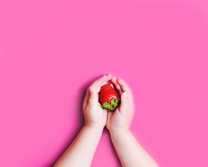 Child's hand holding strawberry on pink background,