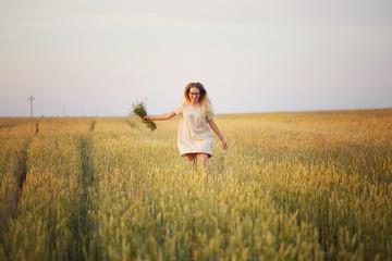 girl with flowers walking on a grain field.