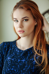 Portrait of a beautiful young woman with red hair near the window