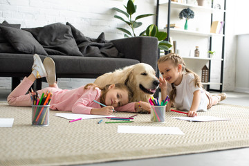 smiling kids lying on floor together with golden retriever dog at home