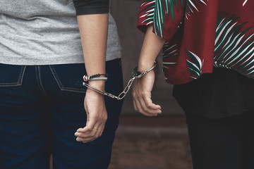 Couple Friend of Women under Arrest, Criminal Scence of Women get Caught with Handcuffed by the Policeman. Concept Picture of Prisoner or Slave. - fototapety na wymiar