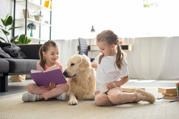 little sisters with books and golden retriever dog near by sitting on floor at home