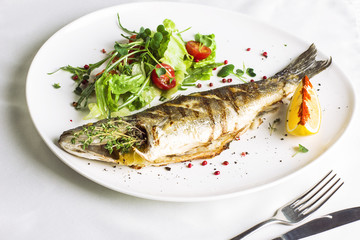 Baked fish with lemon and fresh vegetables on white plate