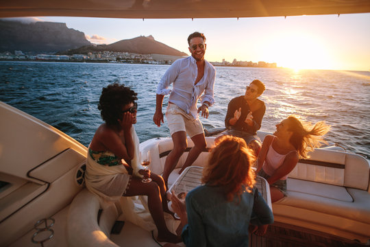 Group of young people dancing in boat party