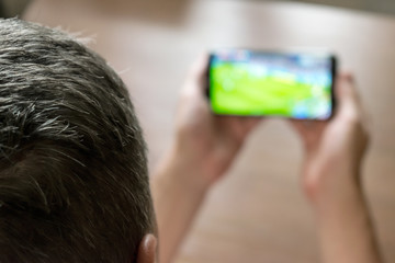 Soccer watching on smartphone tv defocused view. Live broadcast sport channel,  football score live report on mobile phone application. Man watching live soccer game on mobile smartphone at home.