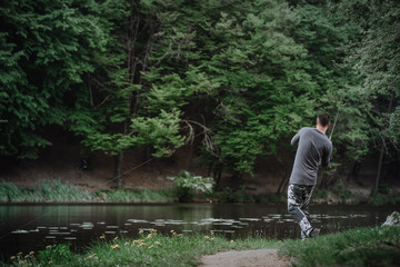 Fisherman cast fishing rod in lake or river water. Man with spinning tackle in green forest. Healthy lifestyle.