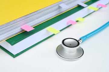 close up of stethoscope with notebook for background