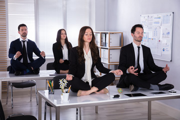 Businesspeople Meditating In Office