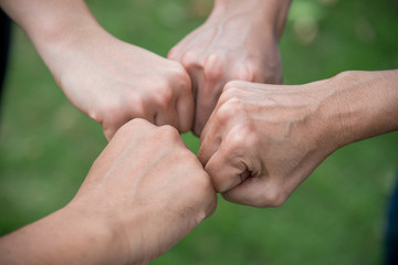 people put their hands together showing teamwork power