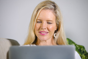 close up portrait of beautiful and happy elegant blond woman early 40s relaxed at home living room using internet on laptop computer working