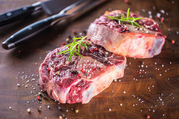 Two raw pieces beef shank on wooden butcher board with fork and knife.