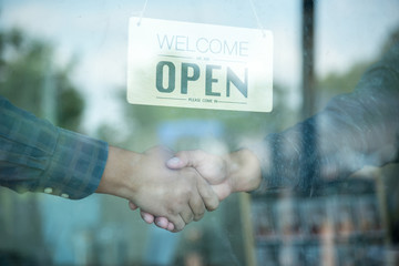 businessman are shaking hand in shop with open sign board through the glass of window