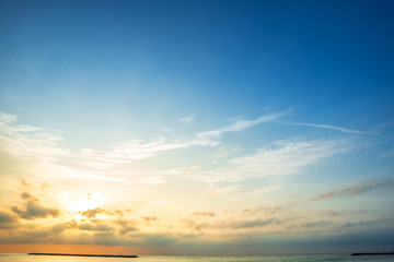 Beautiful early morning sunrise over the sea the horizon,blue sky background texture with white clouds sunset.