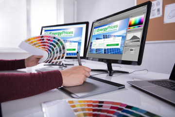 Designer Working On Multiple Computer Screens
