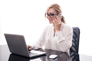 Donna d'affari seduta alla scrivania mentre parla al telefono su fondo bianco