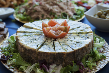 Aged blue cheese wheel with wedge, cut in small triangles at a buffet restaurant, a very distinctive flavor dairy, served as tapas or appetizer