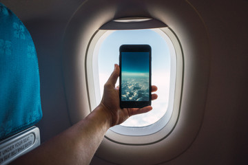 Traveler taking photo of clouds from plane